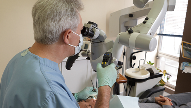 Dr Pizem with a Dental Operating Microscope