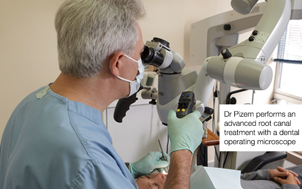 Dr Pizem performing a root canal treatment under operating microscope